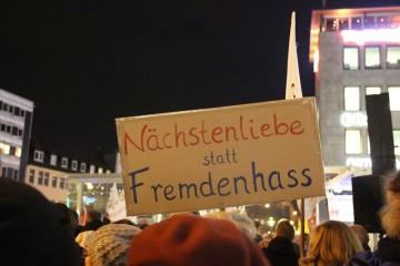 """Bild einer abendlichen Demonstration gegen Pegida, man sieht ein Schild mit der Aufschrift """"Nächstenliebe statt Fremdenhass"""", das in die Höhe gestreckt wird."""