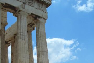 Nahaufnahme eines historischen Gebäudes im griechischen Baustil vor blauem Himmel.