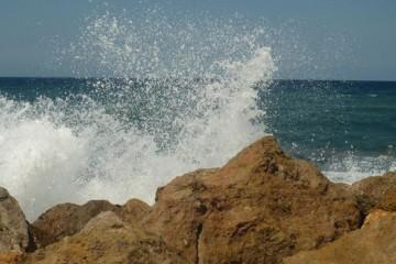 Eine Welle bricht sich am felsigen Ufer, das Wasser spritzt hoch.