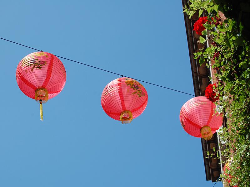 Aus der Froschperspektive fotografierte rote, chinesische Lampions vor blauem Himmel.