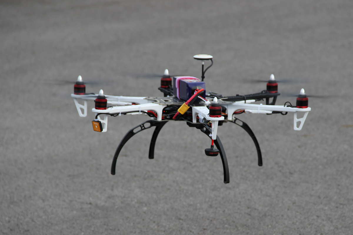 Bild einer kleinen im Flug befindlichen Drohne mit Videofunktion, im Hintergrund Asphalt.