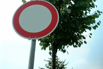 """Verkehrsschild """"Durchfahrt verboten"""" vor einem Laubbaum."""