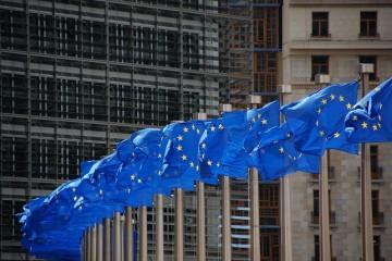 Mehrere EU-Flaggen wehen an Fahnenmästen, im Hintergund ein Gebäude der EU-Kommission in Brüssel.