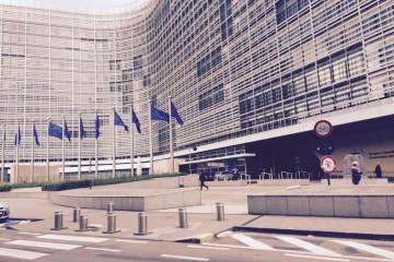 Blick von der Straße auf das Gebäude der EU-Kommission in Brüssel, Eu-Flaggen wehen vor dem Gebäude.