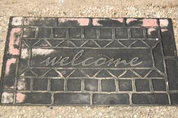 """Fußmatte aus schwarzem Gummi mit Schriftzug """"welcome""""."""