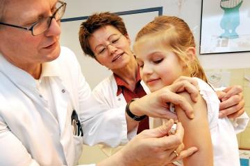 Ein Kinderarzt verabreicht einem jungen Mädchen eine Impfung in den Oberarm, eine Ärztin sieht dabei zu.