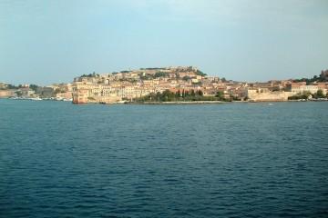 Blick vom Wasser aus auf eine felsige Küstenstadt in Italien.