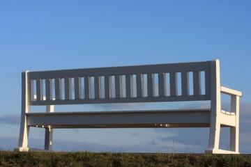 Lange weiße Holzbank vor blauem Himmel.