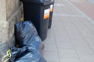 Auf einem Bürgersteig stehen graue Mülltonnen, daneben liegen graue Müllsäcke.