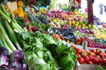 Blick auf einen bunten Marktstand mit verschiedensten Obst- und Gemüsesorten im Angebot.