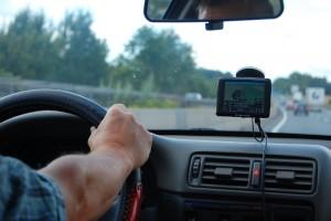 Blick vom Rücksitz in die Auto-Fahrerkabine auf den Arm des Fahrers am Lenkrad und das Navigationsgerät an der Windschutzscheibe.