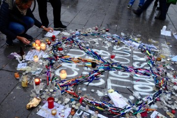Auf einem Gehweg in Paris liegen Zeitungsausschnitte, Blumen und Kerzen in Gedenken andie Opfer des Anschölags auf die Redaktion der Satirezeitschrift Charlie Hebdo.