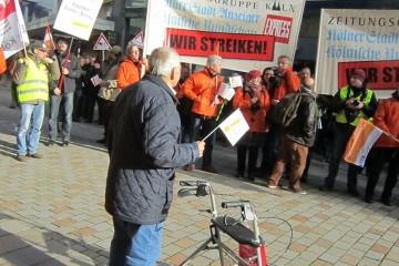 Streikende mit Plakaten in einer Innenstadt, ein Passant schaut zu.