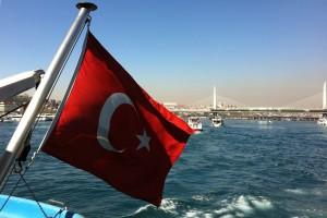 Türkische Staatsflagge am Bug eines Schiffes, mit Meer und Brücke im Hintergrund.