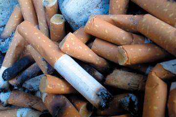 Nahaufnahme von in einem Aschenbecher ausgedrückten Zigarettenstummeln.