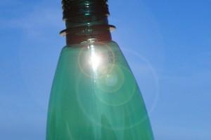 Nahaufnahme einer grünen Plastikflasche mit blauem Himmel im Hintergrund.