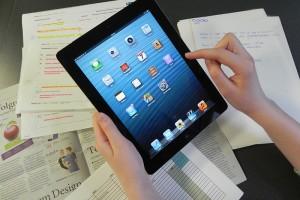 Weibliche Hände halten ein iPad und tippen darauf, im Hintergund liegen verschiedene Unterlagen.