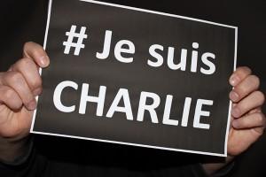 """Jemand hält ein schwarzes Schild mit der weißen Aufschrift """"#Je suis Charlie"""" hoch."""