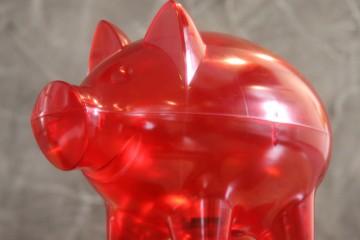Nahaufnahme eines transparenten roten Sparschweines aus Plastik.