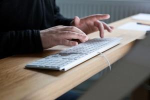 Bildausschnitt: Mann tippt auf einer modernen Computer-Tastatur.