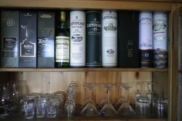 Ein Hiolzregal mit verschiedenen Spirituosen und Gläsern.