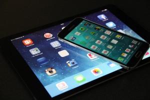 Vor dunklem Hintergrund liegen ein Tablet und darsuf ein Smartphone, auf beiden Geräten sind verschiedene Apps zu sehen.