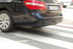 Bildausschnitt: man sieht das Heck eines schwarzen Autos, das offensichtlich zu schnell über einen Zebrastreifen fährt.