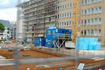 Blick durch einen Bauzaun auf eine Baustelle an einem großem Gebäude.