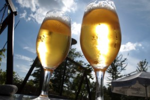 Zwei aus der Froschperspektive aufgeniomme Tulpengläser mit Bier in der Sonne.