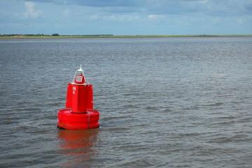Eine rote Boje im Meer, am Horizont ist Land zu sehen..