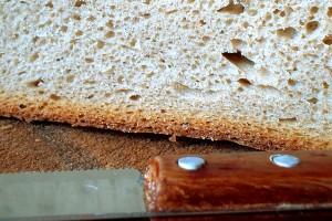 Nahaufnahme eines hellen Brotes auf einem Holzteller, vor dem Brot liegt ein Messer mit Holzgriff.