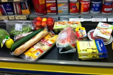 Bildausschnitt zeigt einen Teil eines großen Einkaufs auf dem Kassenband eines Supermarktes.