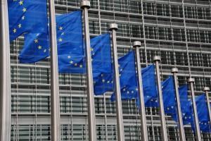 Bildausschnitt mehrerer EU-Flaggen, die an Fahnenmästen wehen, im Hintergund ein Gebäude der EU-Kommission in Brüssel.
