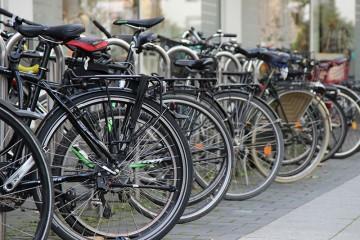 Eine ganze Reihe parkender Fahrräder, im Bildausschnitt sieht man vor allen Dingen die Hinterreifen der Räder.