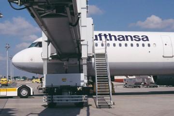 Blick von unter der Gangway auf ein Lufthansa-Flugzeug.