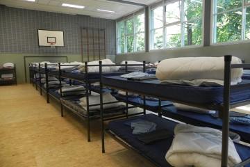 Blick in eine Turnhalle, die mit vielen doppelstöckigen Feldbetten zu einer Flüchtlingsunterkunft umgebaut wurde.