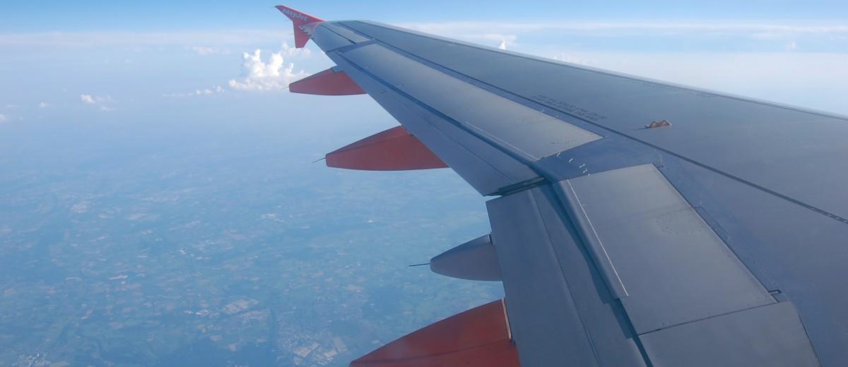 Blick aus dem Flugzeugfenster auf die Tragfläche, man sieht im Hintergrund etwas Landschaft, eine Wolke und den Himmel.