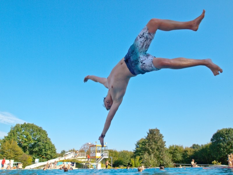 Bild eines Jungen, der bei strahlend blauem Himmel kopfüber in das Becken eines Freibades springt.