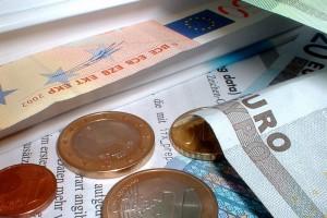 Nahaufnahme einiger Euro-Gelscheine und-Münzen nebst Unterlagen.