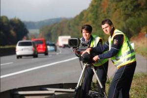 Zwei Polizisten mit gelben Warnwesten stehen mit einem mobilen Blitzer an einer Landstraße und führen Geschwindigkeitskontrollen durch.