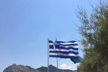 Eine griechische Flagge weht im Wind, im Hintergrund ist hügeliges Gelände und blauer Himmel zu sehen.