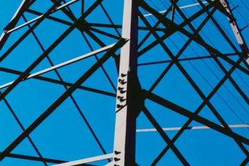 Detailaufnahme eines Hochspannungsmastes aus der Froschperspektive vor blauem Himmel.
