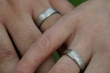 Detailaufnahme der Hände eines Brautpaares mit den silbernen Eheringen am Ringfinger.