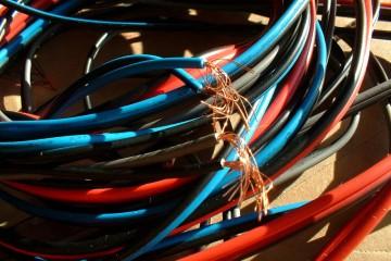 Detailaufnahme von dünnen schwarzen, roten und blauen Kabeln, die gemeinsam aufgerollt wurden und anderen offenen Enden Kupferdrähte hinausragen.