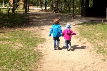Zwei kleine Kinder laufen bei einem Spaziergang Hand in Hand vor dem Fotografierenden her in Richting Wald.