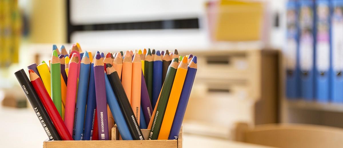 Mehrere farbige Buntstifte in einer Holzkiste