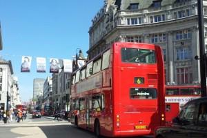Bild von einem der brühmten roten Doppeldeckerbusse, der durch London fährt.