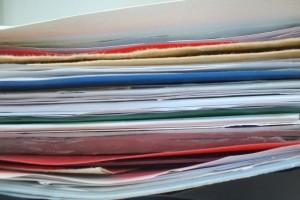 Nahaufnahme eines Stapels bunter Pappmappen, gefülltmit vielen Blatt Papier.