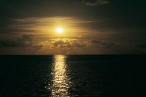 Bild eines Sonnenunterganges über dem dunklen Meer.