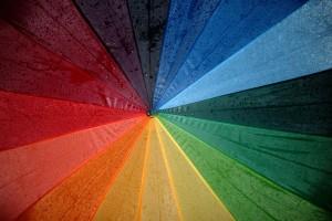 Bild von oben auf einen bunten Regenschirm in Regenbogenfarben.